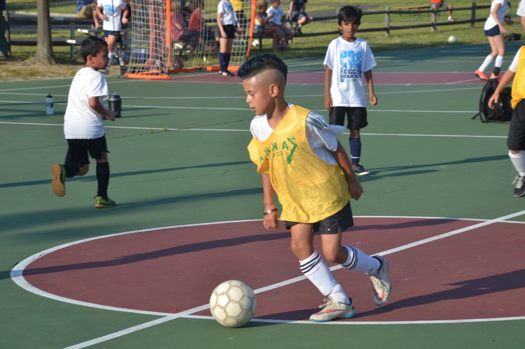 Cherry Hill resident, Christian Mancheno, 8, moves the ball down the court during the AKKA Street Futsal League organized free play on Wednesday, June 22 at Freedom Park in Medford.