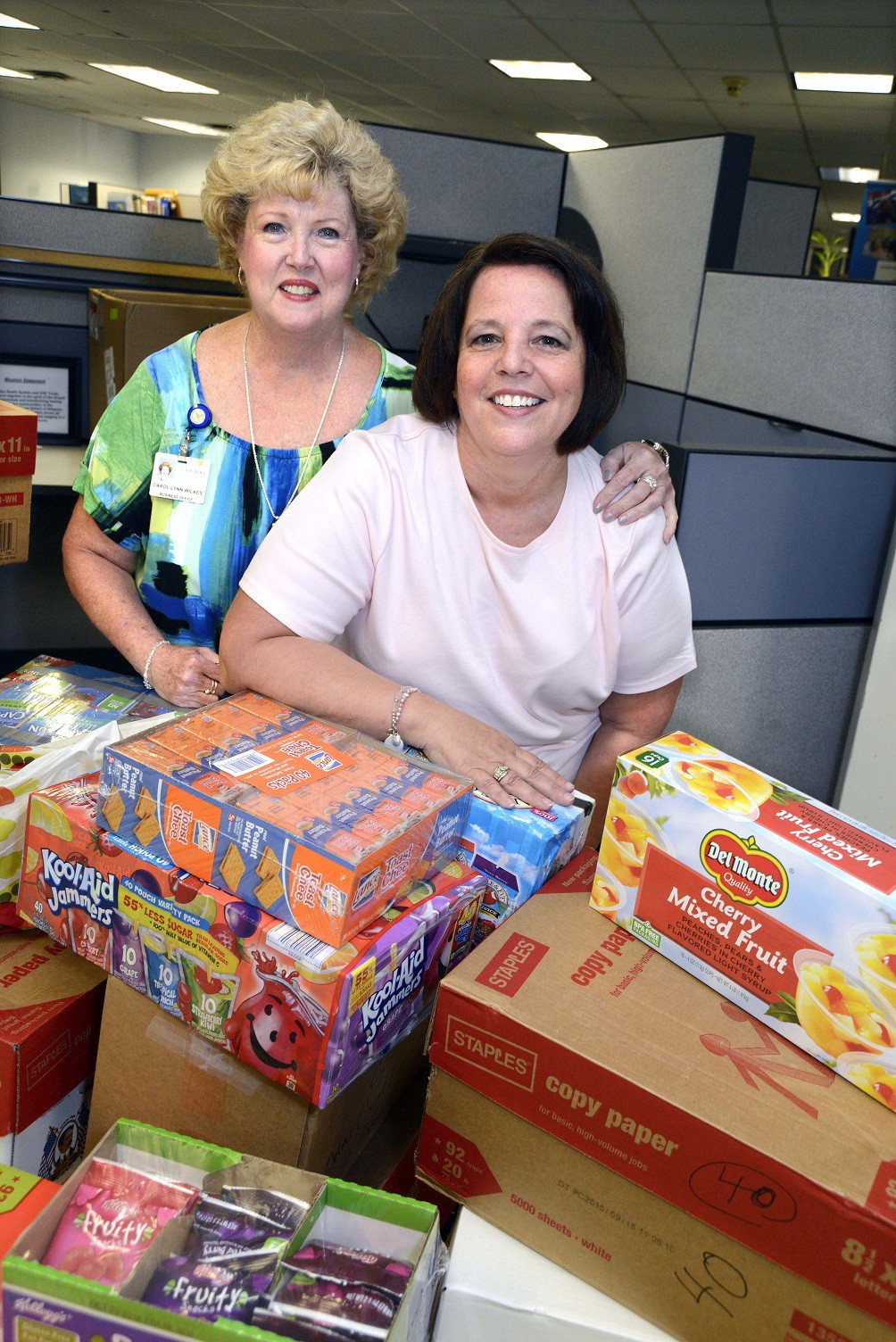 Lourdes' Carol Lynn Wilkes (left) and Annette Gubernick gather food items to donate to Angels of God (AOG) Community Outreach Summer Food Program.
