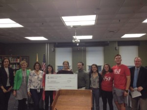 HEF gives check to a teacher at the meeting